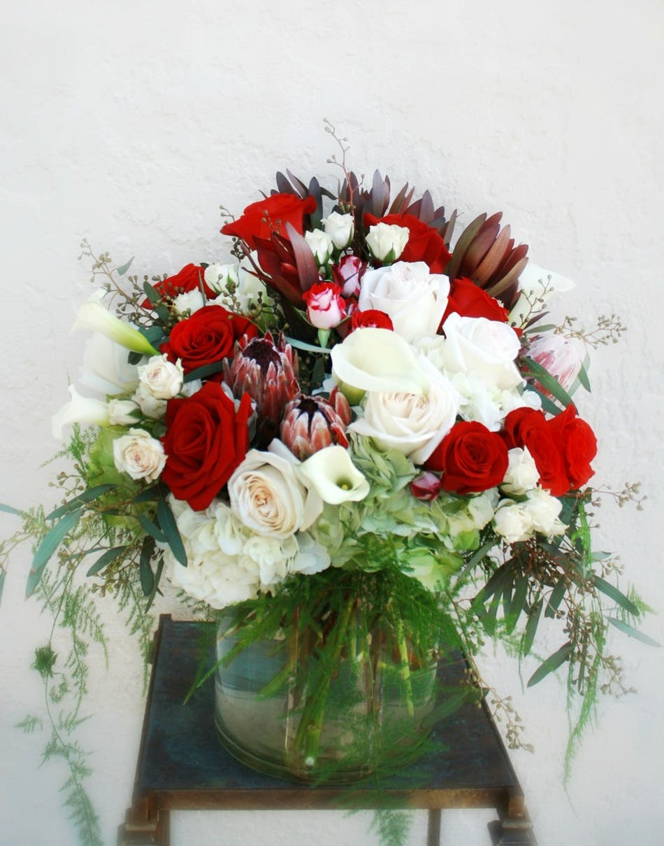 Flowers that express your love port charlotte florist blog this gorgeous design includes calla lilies velvety red roses fragrant garden roses pink mink protea and rich lavish green ferns in a wide cylindrical mightylinksfo