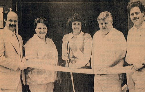 A newspaper clipping of Robert Gill and family, cutting the ribbon outside their new location in the early 1980s